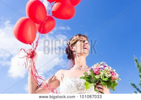 Bride at wedding with read helium balloons