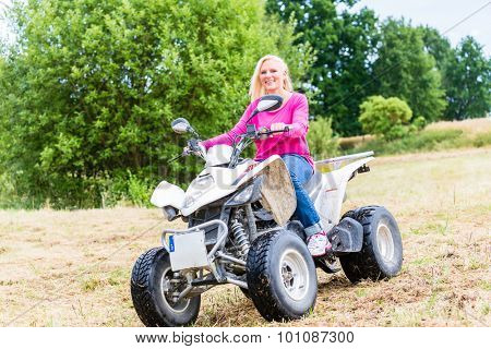 Woman driving off-road with quad bike or ATV