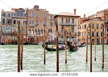 VENICE, ITALY - SEPTEMBER 2014 : Gondoliers carrying tourists on Grand Canal crossing to the Palazzo Salviati in Venice, Italy on September 15, 2014. Gondola boats is the main transportation in Venice