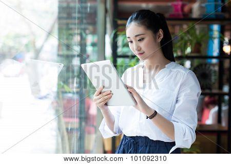 Beautiful Female Using Digital Tablet In Cafe