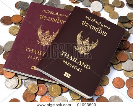 Two Passport  Of Thailand Put On The Pile Of Coins Baht Currency On White Background.
