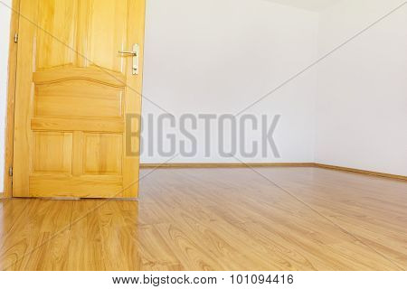 Empty Room With White Walls And Wooden Laminate And Open Wooden Door