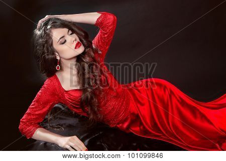 Woman In Red Lying In The Dark. Fashion Tempting Girl Model In Sexy Provocative Gown With Sensual Li
