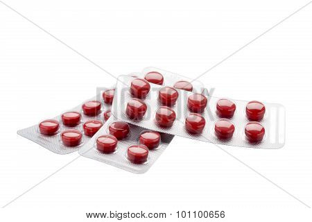 Isolated red pills in blister pack on a white background