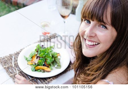 Beautiful woman having salad at restaurant alfresco dining, copy space