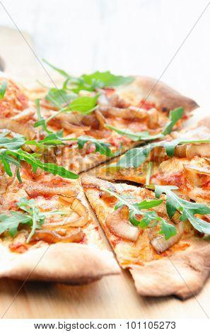 Pizza with tomato, caramelised onion and fresh rocket, fresh handmade thin crust