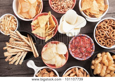 Salty crackers, tortilla chips and other savory snacks with salsa dip