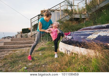 Mother Helping Daughter Stretch On The Beach Using Upturned Boat