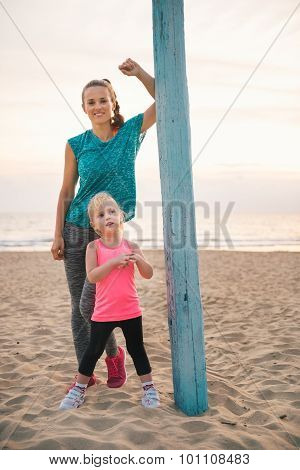 Mother Leaning Against Flagpole Standing Behind Daughter