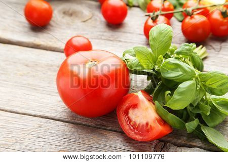 Tomatoes And Basil Leaves On Grey Wooden Background