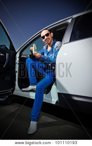 Gangster with cigar and dollars in the car