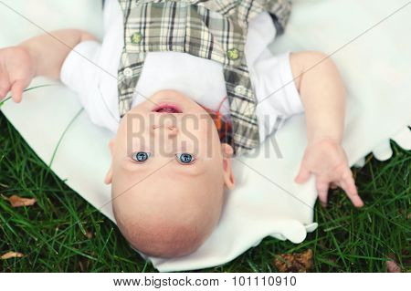 Top view of little cute blue-eyed baby boy lying on back at grass and looking at camera