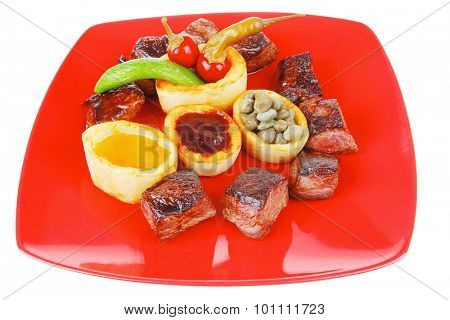 european food: roast beef meat over red plate isolated on white background with hot peppers, capers , olives oil , and bbq sauce