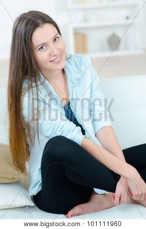 Woman sat on the sofa barefoot