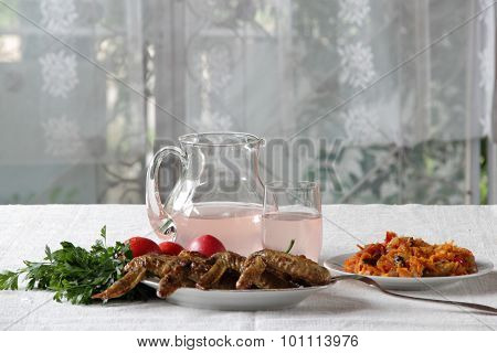 Chicken Wings Fried On A Brazier Submitted With Greens And Vegetables And Compote In A Jug