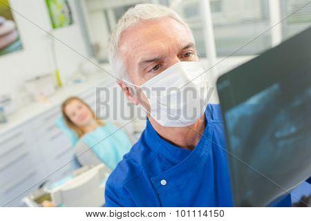 Senior dentist holding up an x-ray