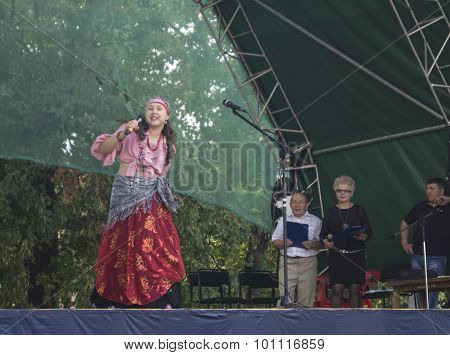 Mstera,Russia-August 8,2015: Girl in gipsy cloth sings on scene at day of the city Mstera,Russia