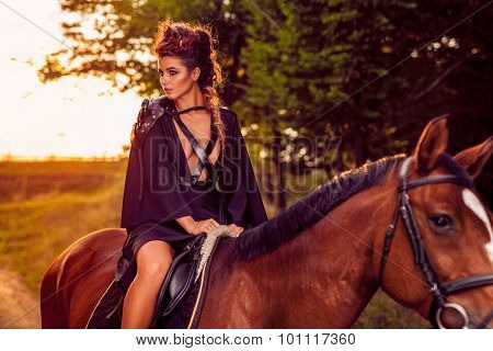 Beautiful young fashion model with horse shot at sunset