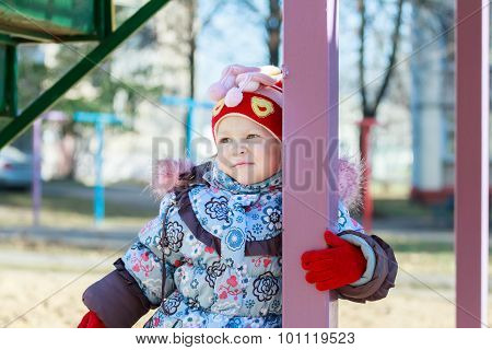 Portrait of nursery school girl in warm autumn kids wear is standing among playground