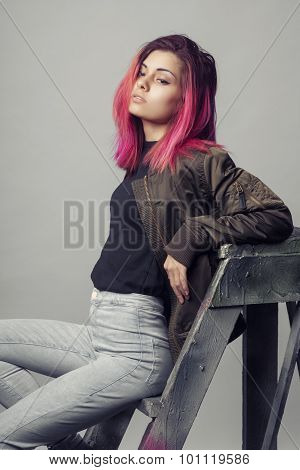 young woman in jacket and blue jeans with pink hair studio shot