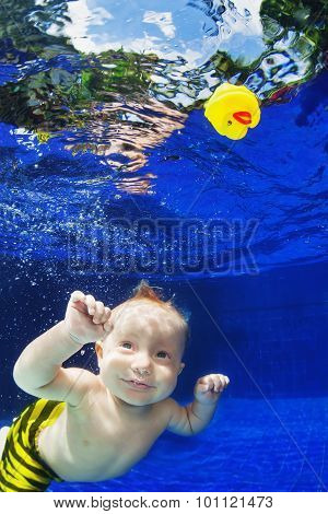 Child Swimming Underwater In Blue Pool For Yellow Toy