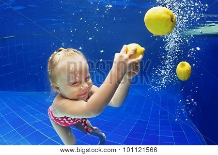 Child Swimming Underwater In Blue Pool For Yellow Lemon