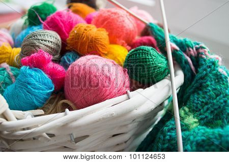 Multicolored clews in wicker basket with plaid closeup
