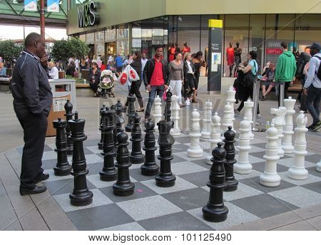 LONDON- 9 SEPT: Men playing a game of giant chess at the new westfield shopping centre in stratford, east london. LONDON, 9 SEPT, 2015.