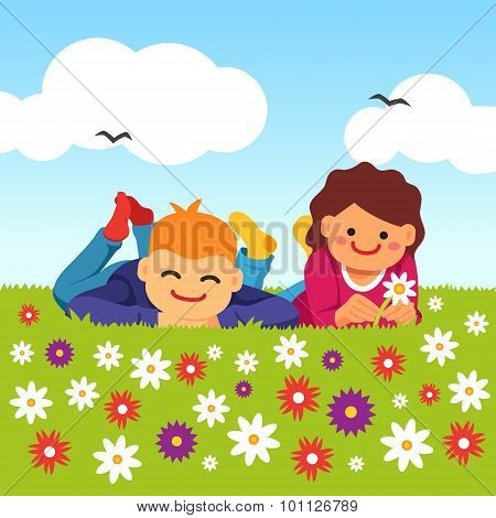 Happy kids laying on meadow field grass