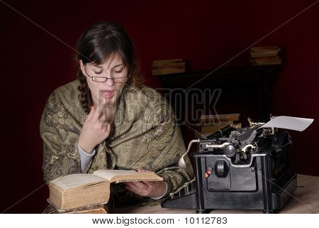 Woman Reading Very Old Books Next To Old Typewriter