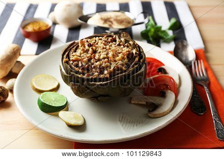 Vegetarian stuffed artichoke on plate, on table background