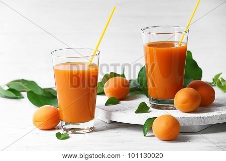 Glasses of apricots juice on wooden table on white background