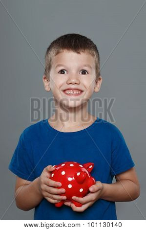 Excited Little Boy Holding Piggy Bank