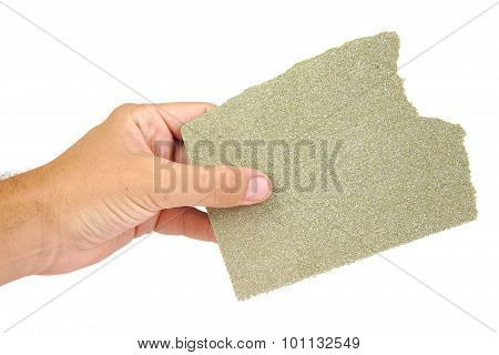 Hand holding sanding sheet isolated on a white background