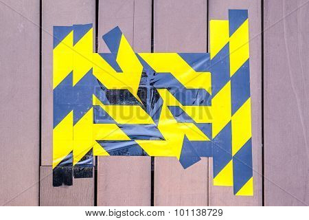 Yellow And Black Caution Tape Marked On Broken Wooden Floor.