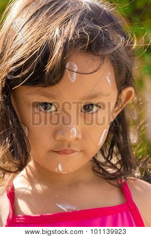 Asian Child with Sunblock Lotion On Her Face