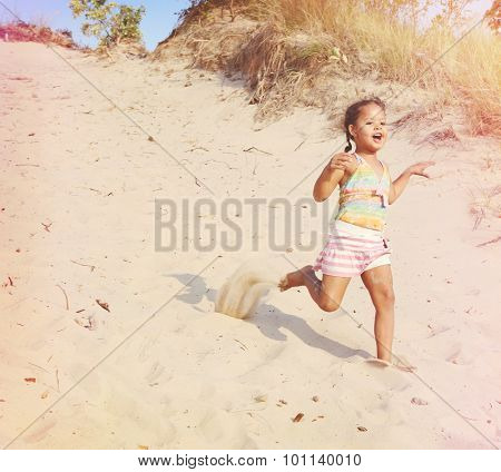 Happy Smiling girl running down the dunes at the beach. Vintage Instagram effect. Some motion blur, focus on girls face.