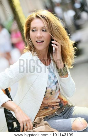 Trendy girl talking on phone in the street