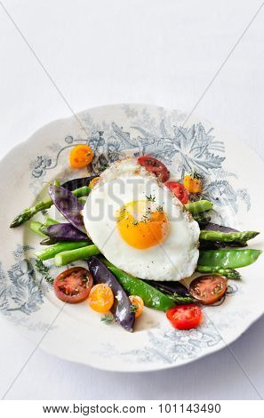 Fried sunny side up egg on healthy colourful spring vegetables asparagus, mange tout, cherry tomatoes, light healthy low carb meal or appetiser