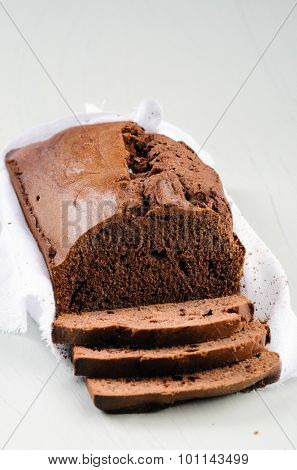 Loaf of chocolate cake wrapped with muslin cloth