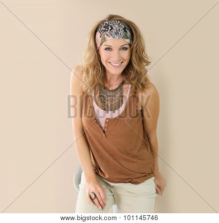 Mature stylish woman standing on beige background, isolated