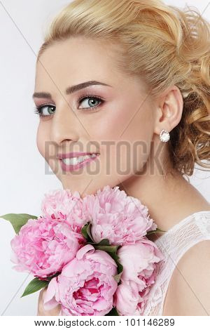 Portrait of young beautiful blonde happy smiling bride with bouquet
