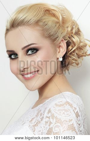 Portrait of young beautiful blonde happy smiling bride in lacy dress