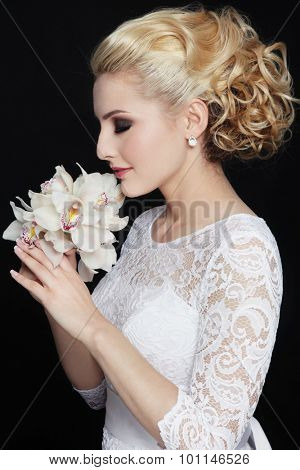 Young beautiful happy slim blonde bride in lacy dress with stylish prom hairdo