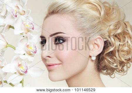 Close-up portrait of young beautiful blond girl with smoky eyes and stylish prom hairdo