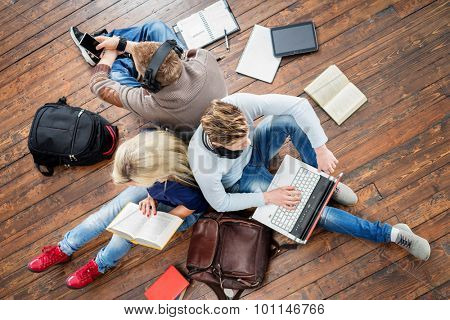 Group of students using smartphones, laptops and reading books in headphones listening to the music and leaning on each other on wooden floor having notebooks and bags around them.