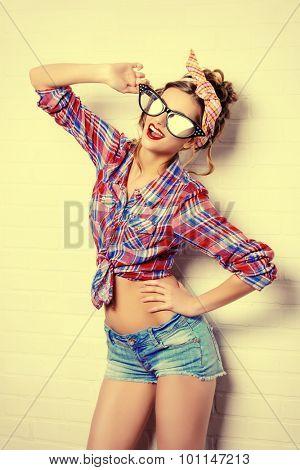 Close-up portrait of a funny glamorous pin-up girl in a huge stylish glasses. Beauty, fashion. Optics, eyewear.