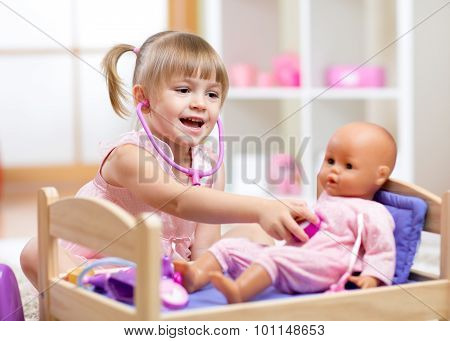 Child in kindergarten. Kid in nursery school. Girl playing doctor with doll