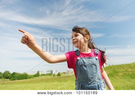 summer, childhood, leisure, direction and people concept - happy little girl pointing finger on green summer field
