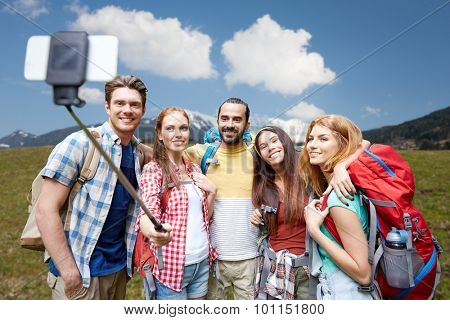 technology, travel, tourism, hike and people concept - group of smiling friends walking with backpacks taking picture by smartphone on selfie stick over natural background